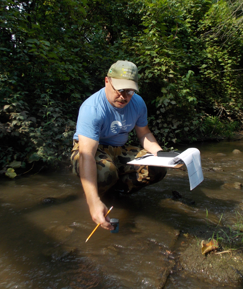 Mark Schaller tests the water in Woods Creek.