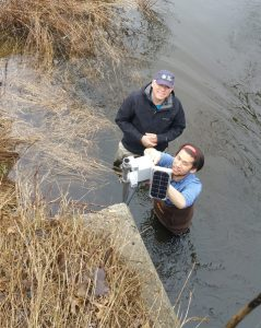 HRWC volunteer Larry and University of Michigan researcher Brandon installing stream sensor equipment.