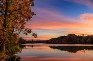 A colorful autumn sunrise is reflected in the Huron River in Ann Arbor, Michigan