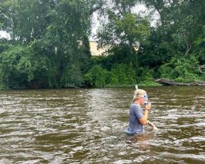 A river snorkeling camper walks in the river wearing a snorkel