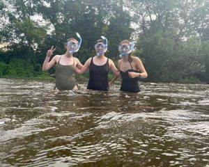 HRWC interns pose in snorkel gear while wading in the river