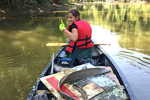 Girl gives thumbs up in canoe during river cleanup